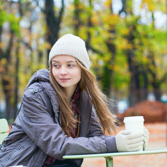 Young Parisian girl drinking coffee in park