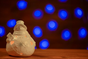 Christmas snowman candle and lights in background