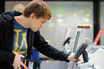Young man using pos terminal at the shop