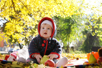 Baby girl sitting among autumn leaves
