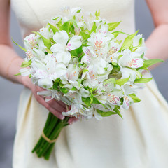 Young bride holding in her hands wedding flowers