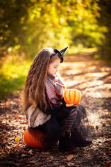 Portrait of a cute girl in the wood with pumpkins.