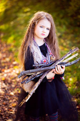 Portrait of a cute girl in halloween costume holding brushwood.