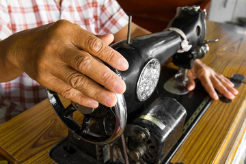 Female hand holding a rotating wheel of the sewing machine test.