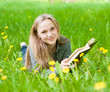 girl lying on grass with dandelions reading a book and looking a