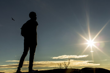 Male silhouette standing on a mountain and taking in the view