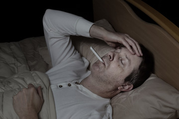 Mature man with high fever in bed