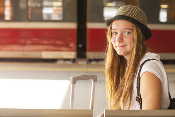 Gute girl traveler waiting for his train at the railway station.