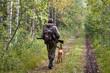 Leinwandbild Motiv hunter with dog walking on the forest road