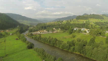 Flight over rural areas with river  in mountains .Aerial  shot