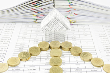 Gold coins as arrow in front of house