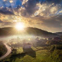 mountain village in fog on sunrise