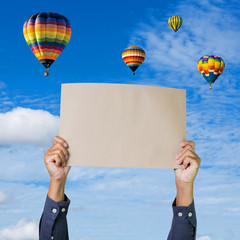 Hands holding banner with hot air balloon and blue sky backgroun