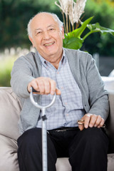Portrait Of Happy Senior Man Holding Metal Cane