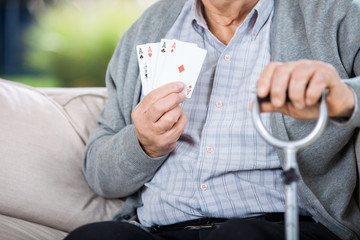 Elderly Man Showing Four Aces While Sitting