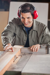 Happy Carpenter Cutting Wooden Plank With Tablesaw