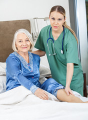 Female Caretaker Checking Senior Woman's Leg