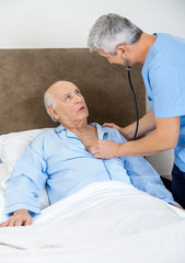 Caretaker Examining Senior Man With Stethoscope