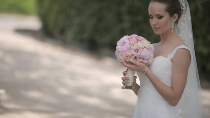 Delicate and beautiful bride stands in the park