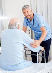 Smiling Caretaker Helping Senior Man With Walking Frame