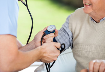 Male Doctor Checking Blood Pressure Of Senior Man