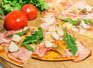 Cooking pizza with arugula and mushrooms