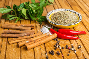spices, mint, cinnamon and pepper  on  wooden table