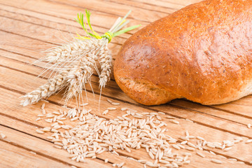 Fresh bread with wheat grains on a wooden  background