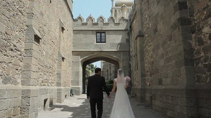 Young bride and groom go through the ancient streets of the