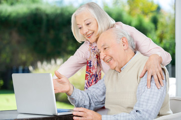 Cheerful Senior Couple Using Laptop
