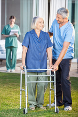 Caretaker Helping Senior Woman To Use Walking Frame