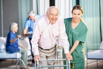 Female Caretaker Helping Senior Man In Using Zimmer Frame