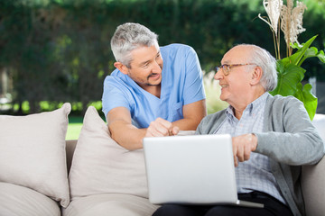Smiling Nurse And Senior Man Using Laptop