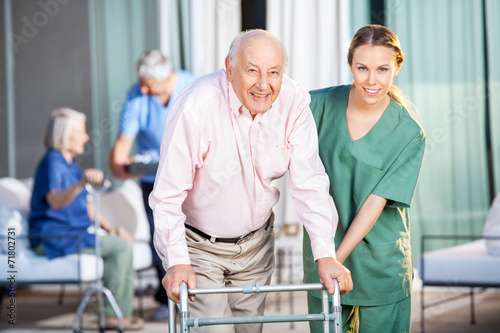 Female Caretaker Helping Senior Man In Using Zimmer Frame - 71802731