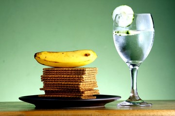 Stack of crackers, banana, goblet of water with cucumber slices
