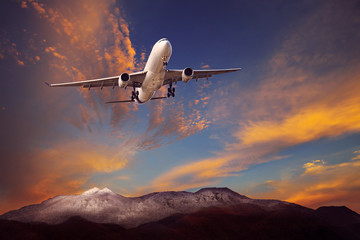 passenger plane flying above rock mountain against beautiful dus
