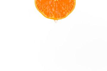 Slice orange drop of juice over white background