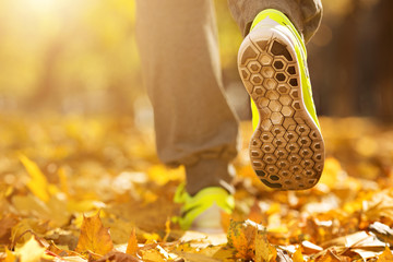 Runner woman feet running on autumn road closeup on shoe. Female