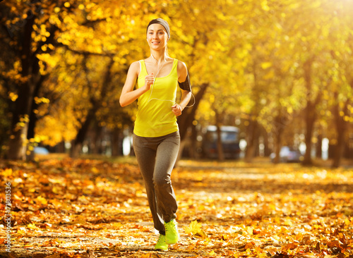 canvas print picture Running woman. Runner is jogging in sunny bright light in the au