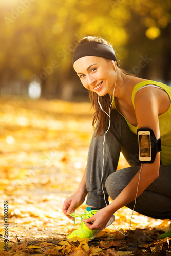 canvas print picture Running woman. Runner is tying laces and listening to music. Fem