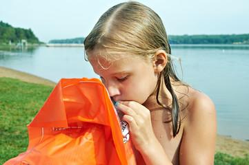 Girl inflates the orange mattress on the beach
