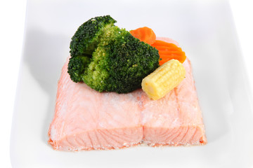Piece of salmon on a plate, steamed, decorated with vegetables.