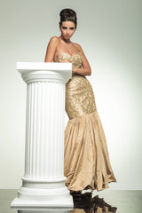 fashion elegant woman in golden dress leaning on a column