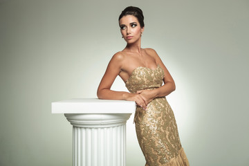 classy young woman in long elegant dress leans on column