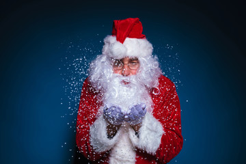 Santa Claus with glasses blowing snow