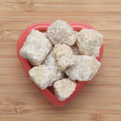 Brown cane sugars in a heart bowl