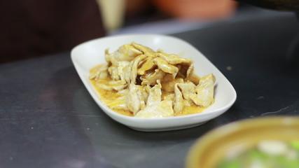 Chef prepares a dish in restaurant kitchen, spicy chicken