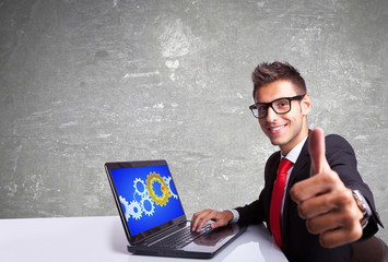 satisfied business man working on laptop and making ok sign