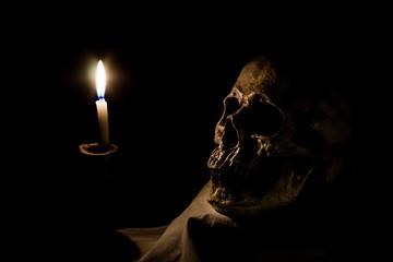 Human skull and burning candle