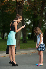 Mother talking to naughty girl on a street in park
